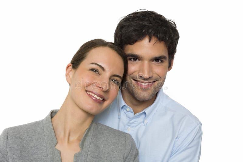 Glückliche junge Liebhaberpaare, die auf dem weißen Hintergrund, lokalisiert stehen lizenzfreie stockfotografie