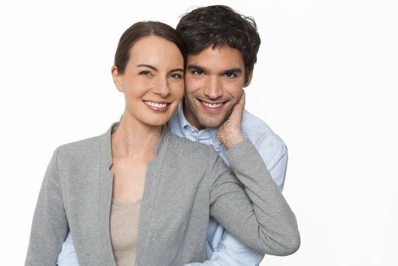 Glückliche junge Liebhaberpaare, die auf dem weißen Hintergrund, lokalisiert stehen stockfotografie