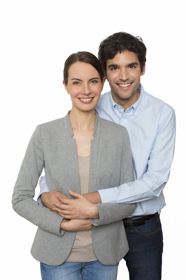 Glückliche junge Liebhaberpaare, die auf dem weißen Hintergrund, lokalisiert stehen lizenzfreies stockbild