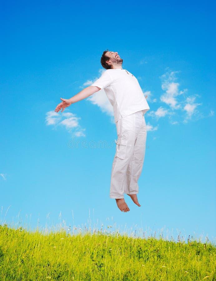 Glückliche junge Mähne im weißem Springen auf schönen mea lizenzfreie stockfotografie