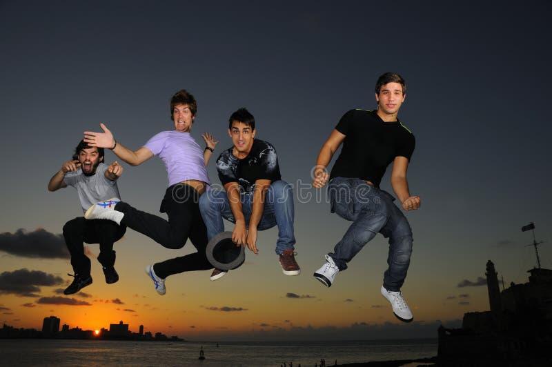 Glückliche junge männliche Gruppe, die am Sonnenuntergang springt stockbild