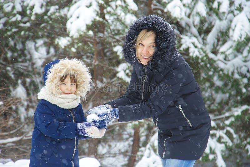 Glückliche junge Mama und ihre kleine Tochter in den Winterhüten im Schneewald am Schneeflockenhintergrund Freienwinterfreizeit u lizenzfreie stockfotografie