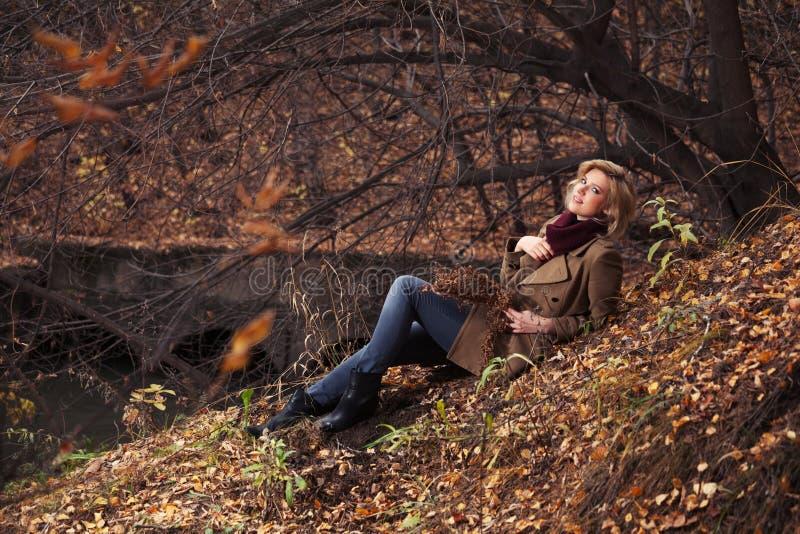 Glückliche junge Modefrau, die auf dem Boden im Herbstpark sitzt lizenzfreies stockfoto