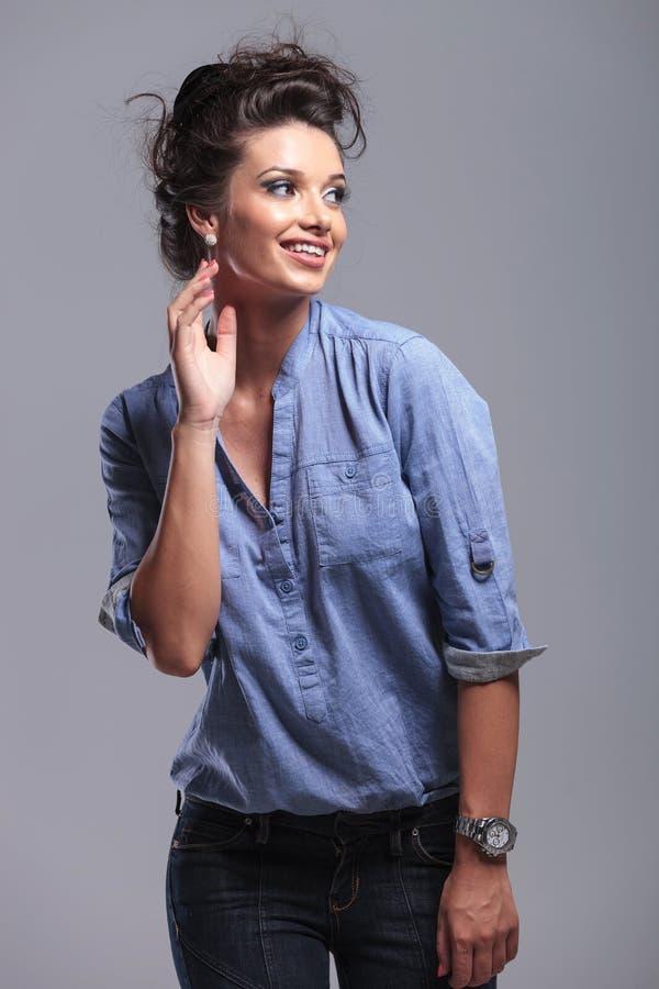 Glückliche junge Modefrau, die ihre Ohrringe zeigt stockbild