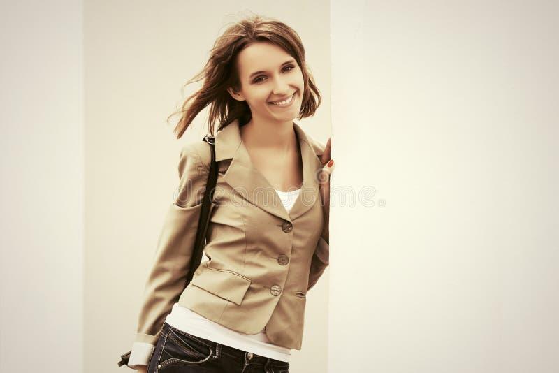 Glückliche junge Modefrau mit der Handtasche, die an der Wand steht stockfotos