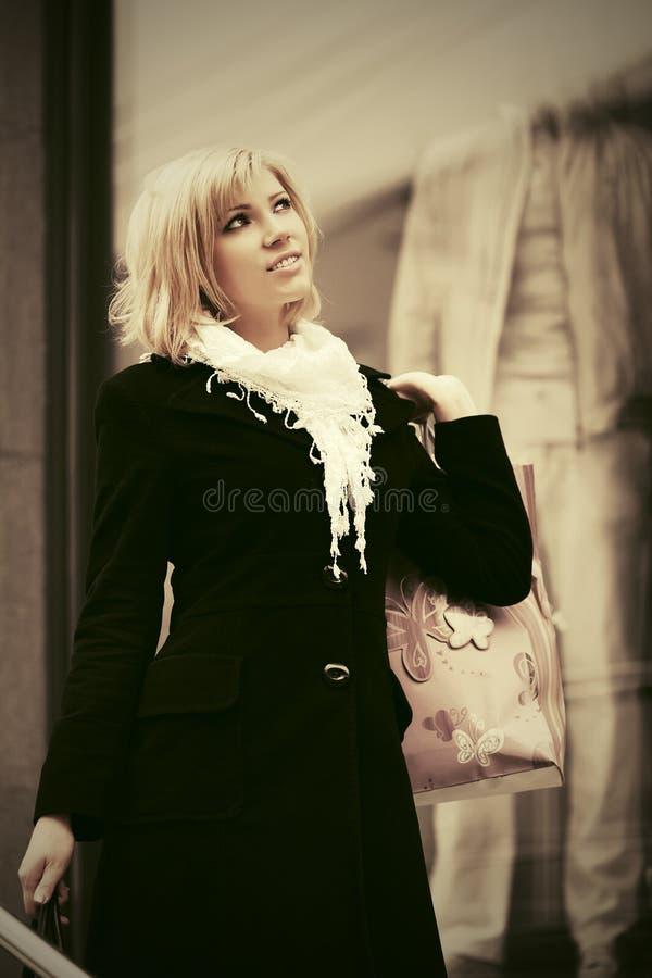 Glückliche junge Modefrau mit Einkaufstaschen nahe bei Mallfenstern stockbild