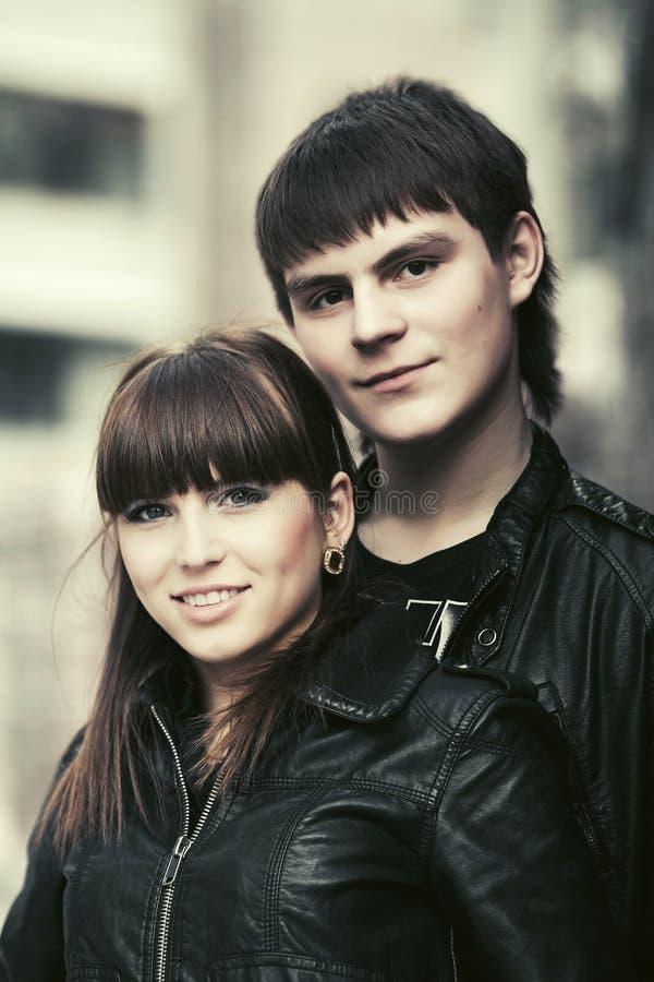 Glückliche junge Modepaare, die in Stadtstraße gehen lizenzfreies stockbild