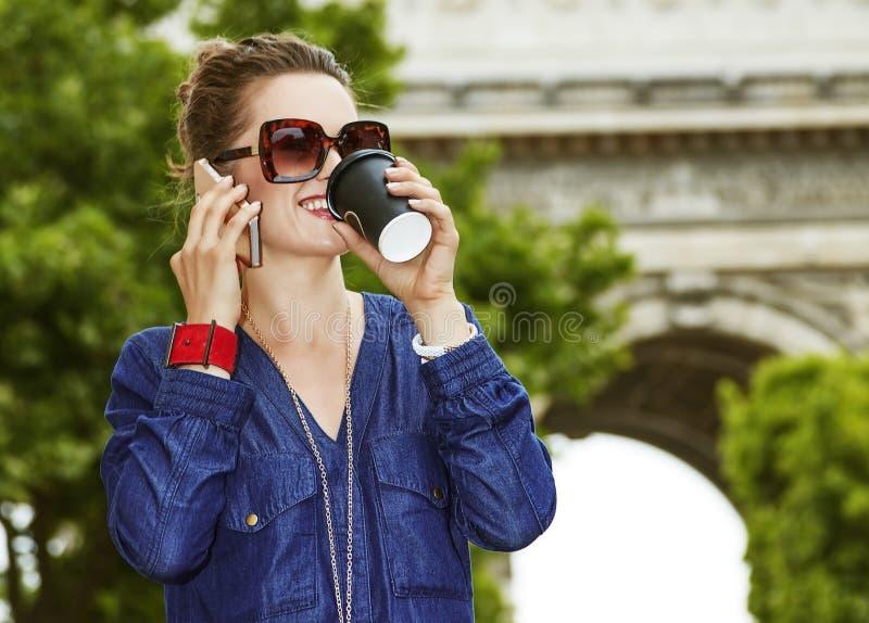 Glückliche junge modische Frau beim Trinken des Kaffees auf Champion Elysees lizenzfreies stockbild
