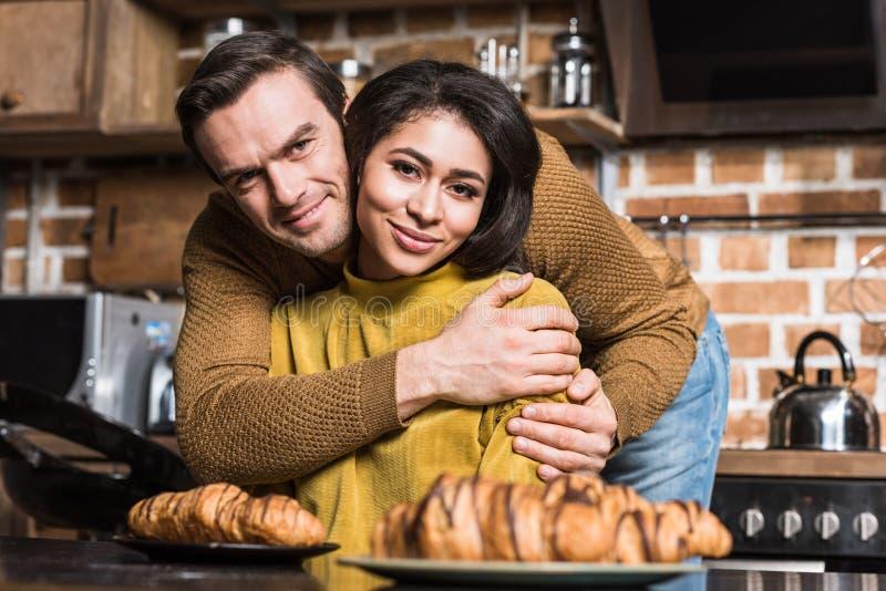 glückliche junge multiethnische Paare, die an der Kamera während des Frühstücks umfassen und lächeln lizenzfreie stockbilder