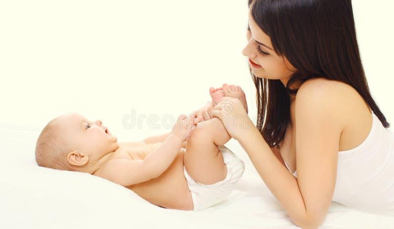 Glückliche junge Mutter der Nahaufnahme, die mit ihrem Baby auf Bett spielt stockfoto