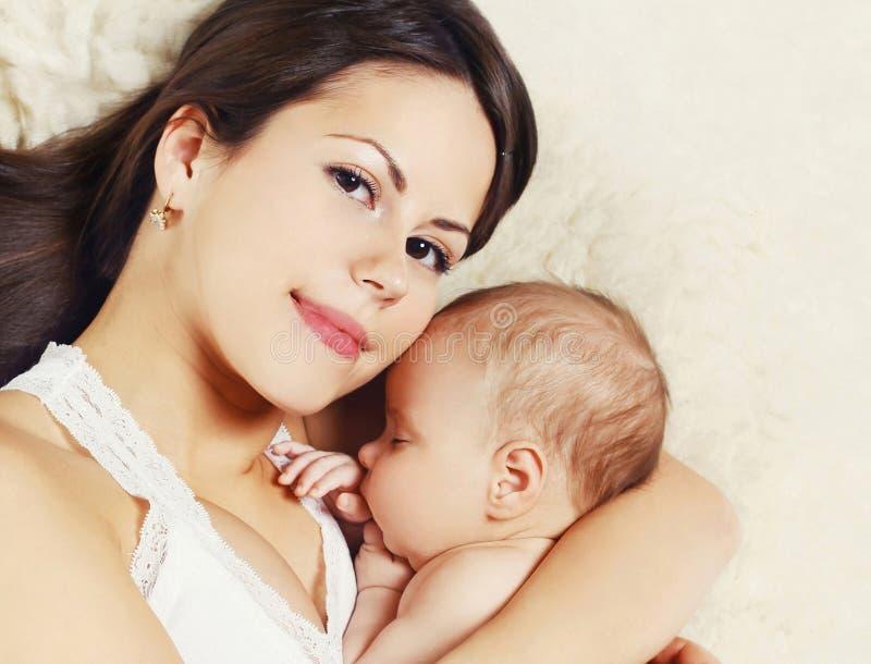 Glückliche junge Mutter der Porträtnahaufnahme und schlafendes Baby auf Bett zu Hause lizenzfreie stockfotos