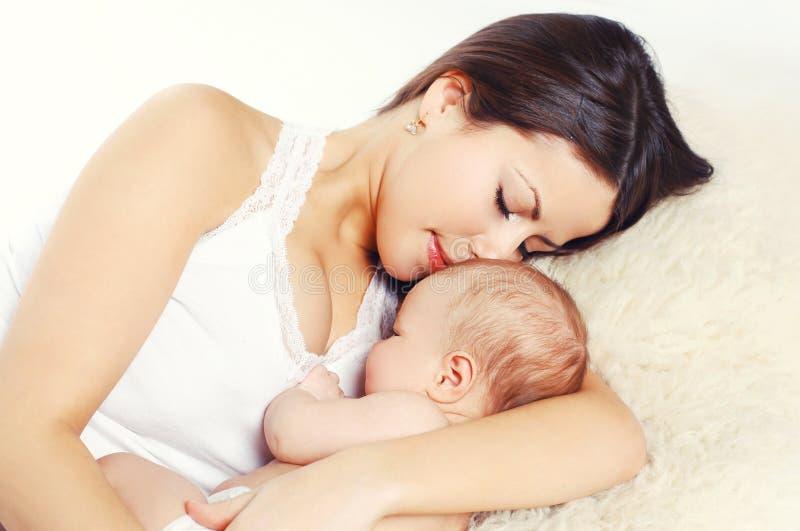 Glückliche junge Mutter des Porträts, die zu Hause mit Baby auf Bett, t schläft stockbilder