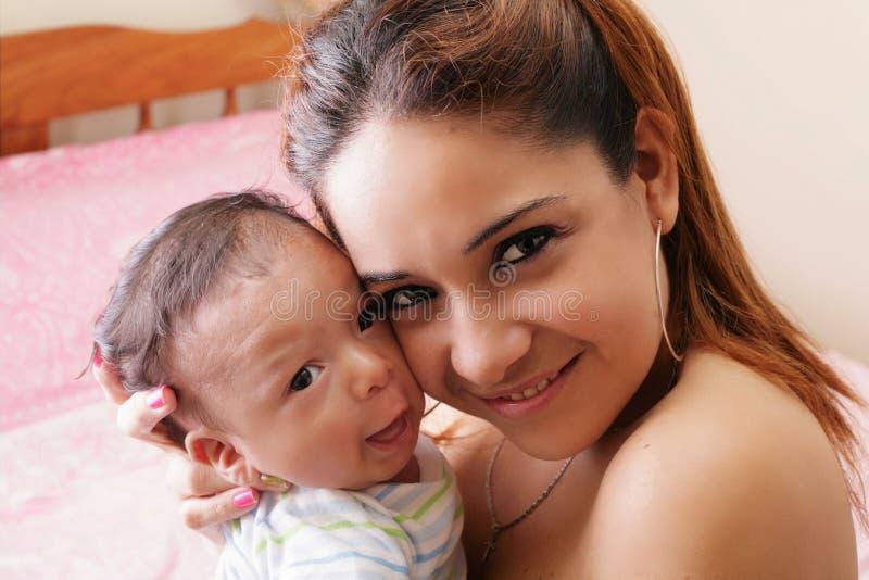 Glückliche junge Mutter, die ein Baby hält stockfotos
