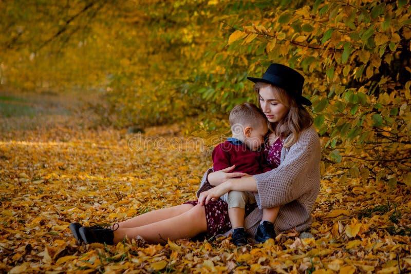 Glückliche junge Mutter, die mit Baby im Herbstpark mit gelben Ahornblättern spielt Familie, die draußen in Herbst geht wenig stockbilder