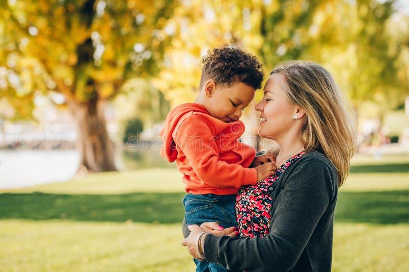 Glückliche junge Mutter, die süßen Kleinkindjungen hält lizenzfreie stockbilder