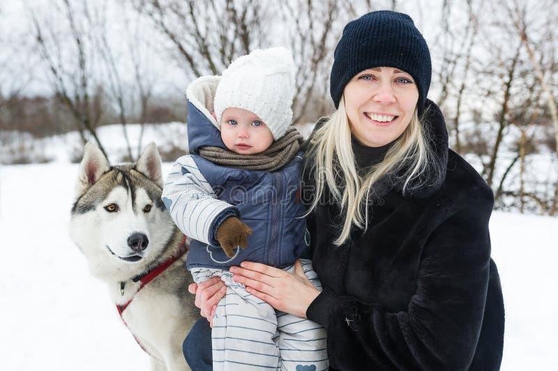 Glückliche junge Mutter mit Tochter im Winterpark mit Schlittenhundhund stockfoto