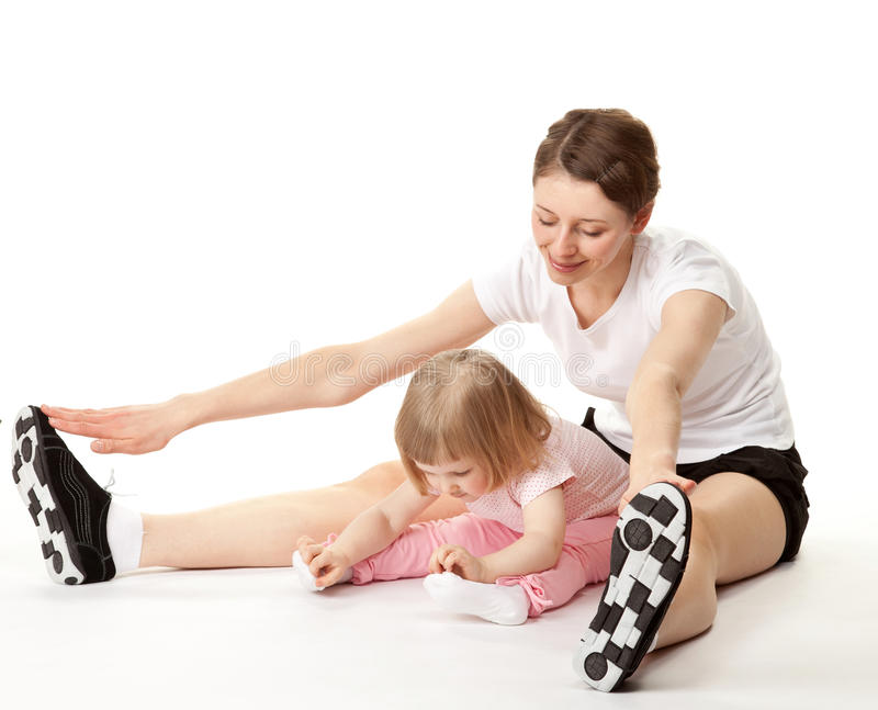 Glückliche junge Mutter und ihre kleine Tochter, die Sportübungen tut stockfotos