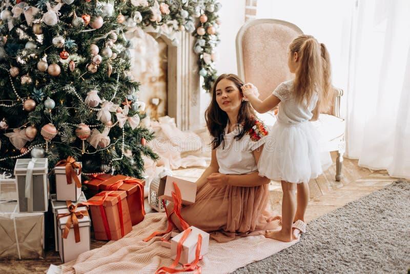 Glückliche junge Mutter und ihre kleine Tochter im hübschen Kleid sitzen nahe dem Baum des neuen Jahres und offenen den Geschen stockfotografie