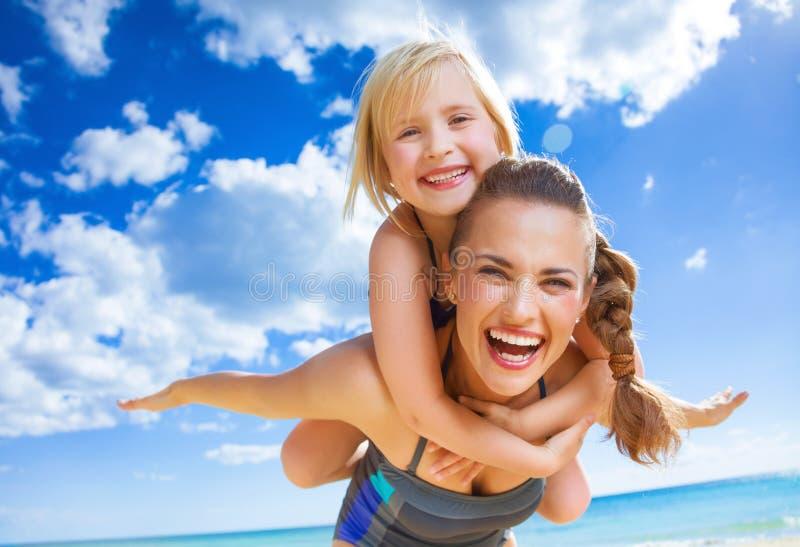 Glückliche junge Mutter und Kind auf dem Strand, der Spaßzeit hat stockfoto
