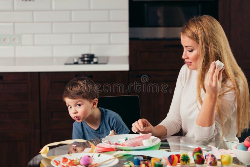 Glückliche junge Mutter und Sohn, die zusammen selbst gemachte Ostereier isst stockfotos