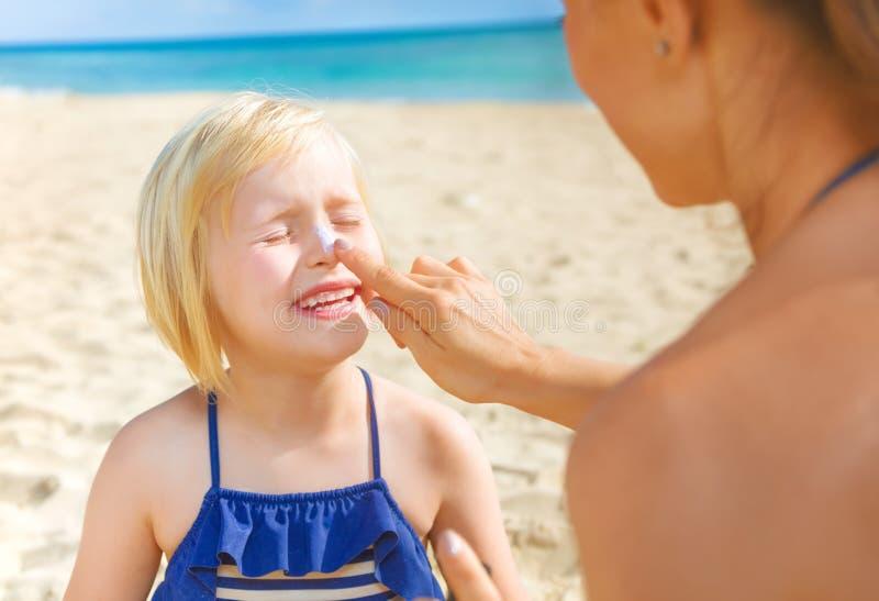 Glückliche junge Mutter und Tochter auf dem Strand, der SPF anwendet lizenzfreie stockfotos