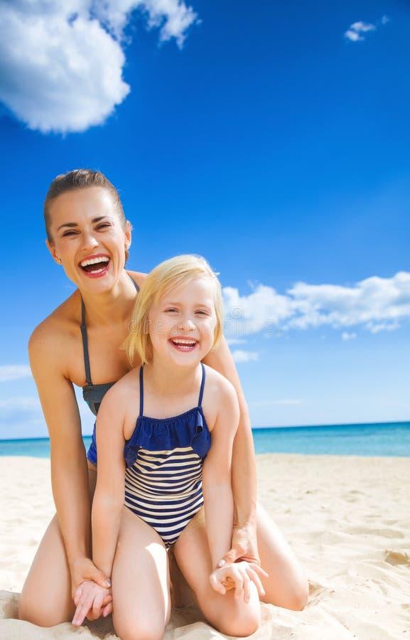 Glückliche junge Mutter und Tochter auf der Seeküste, die Spaßzeit hat lizenzfreie stockfotos