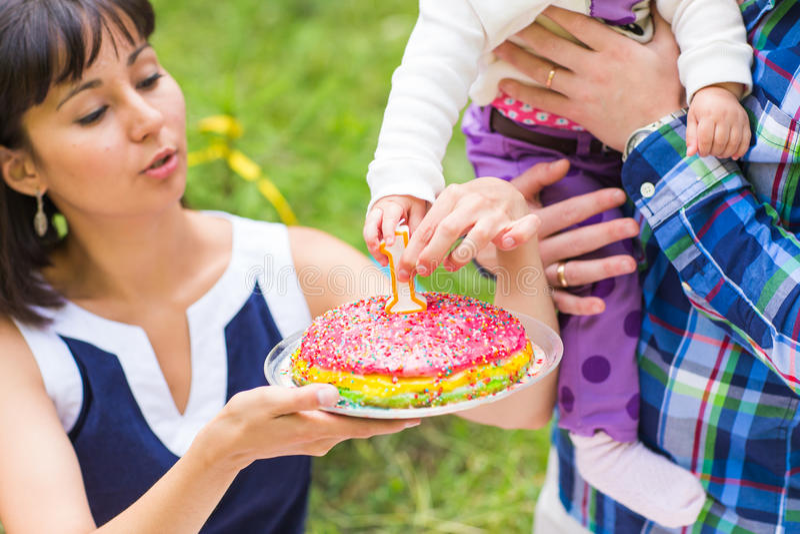 Glückliche junge Mutter und Vater mit ihrer Babytochter, die auf einer Decke in einem Park feiernd mit Geburtstagskuchen sich ent stockfotos