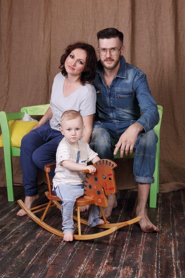 Glückliche junge Mutter, Vater sitzen auf Bank und kleinem Sohn lizenzfreie stockfotografie