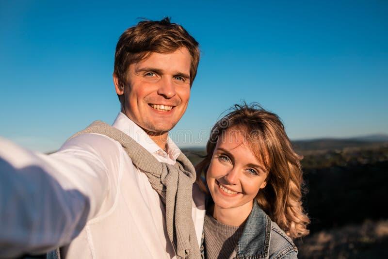 Glückliche junge nette Paare, die draußen selfie machen lizenzfreie stockfotografie