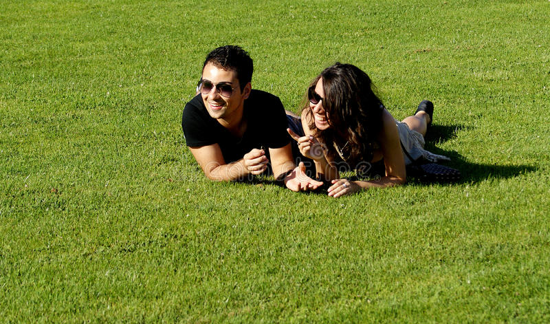 Glückliche junge Paare auf Feld lizenzfreie stockfotos