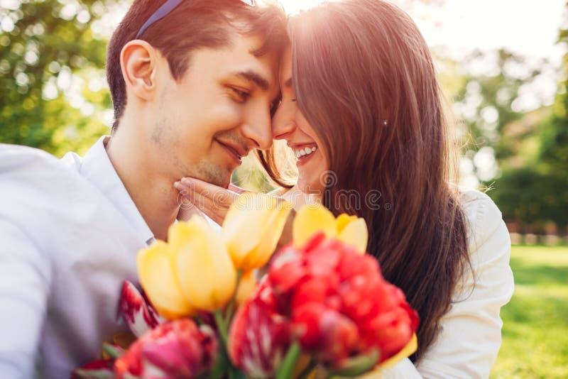 Glückliche junge Paare in der Liebe, die draußen mit Frühlingsblumenblumenstrauß umarmt Mann begabt seine Freundin mit Tulpen lizenzfreie stockbilder