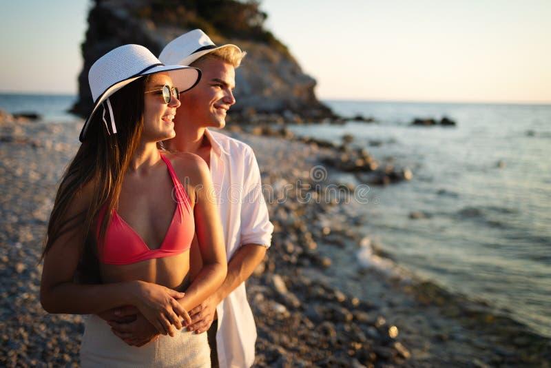 Glückliche junge Paare in der Liebe, die im Urlaub auf Küste geht lizenzfreie stockfotografie