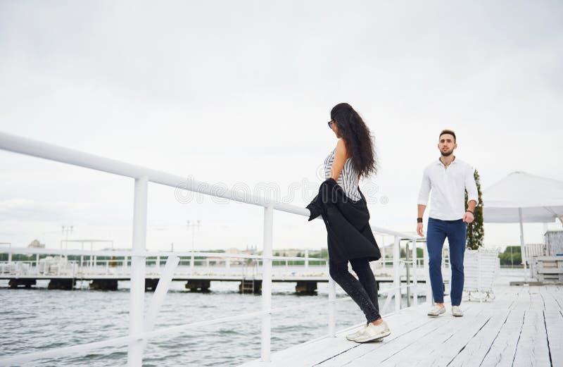 Glückliche junge Paare in der Liebe in einem schönen Kleid, werfend auf dem Pier nahe dem Wasser auf stockbilder