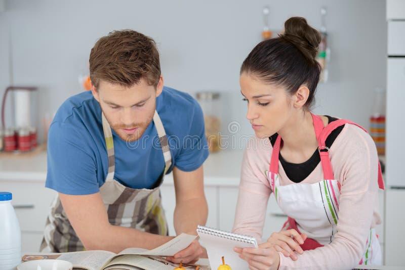 Glückliche junge Paare des Porträts, die zusammen in der Küche kochen lizenzfreies stockbild