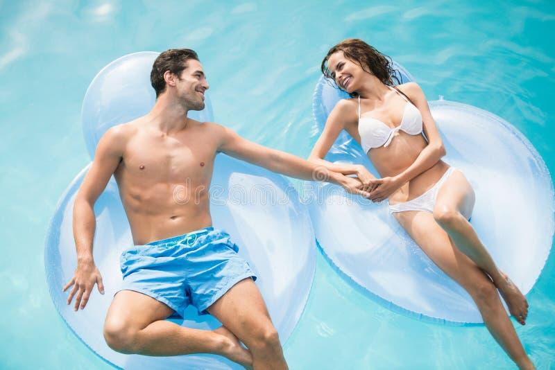 Glückliche junge Paare, die auf aufblasbarem Ring sich entspannen stockfoto