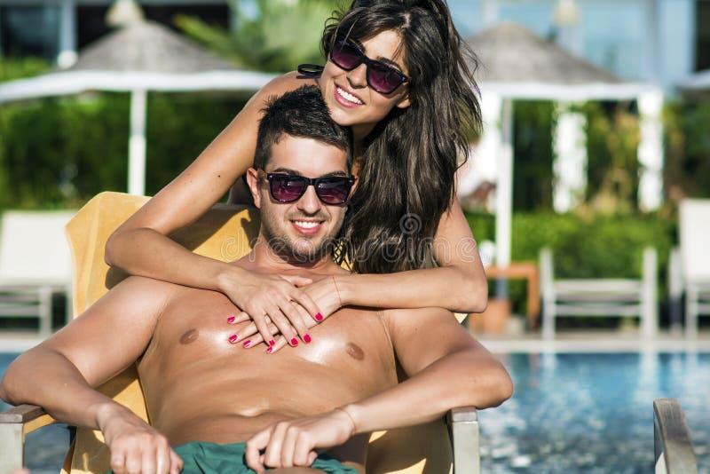 Glückliche junge Paare, die auf dem Pool umarmen und sich entspannen stockfoto