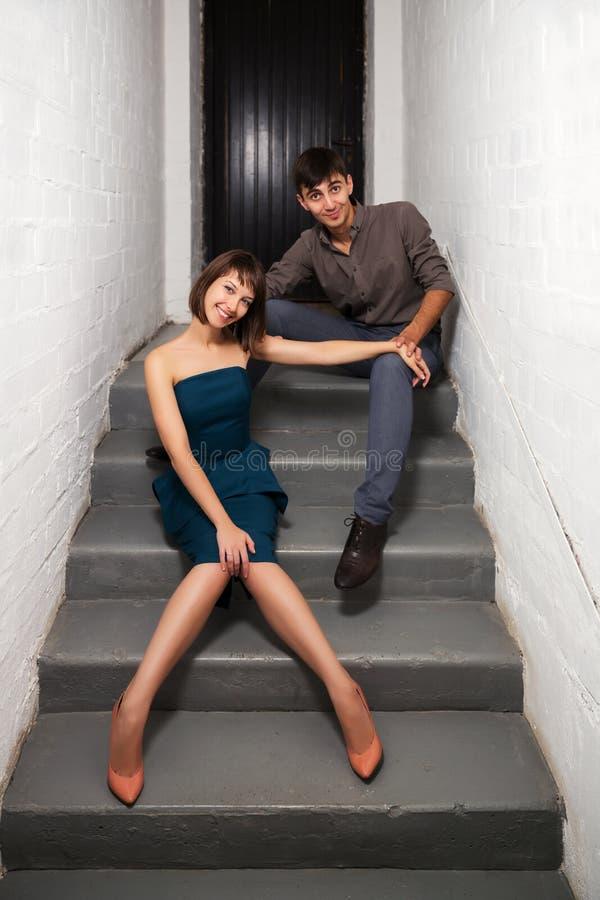 Glückliche junge Paare, die auf den Schritten im Büro sitzen lizenzfreie stockfotos