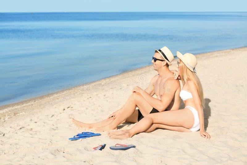 Glückliche junge Paare, die auf Seestrand stillstehen stockfotos