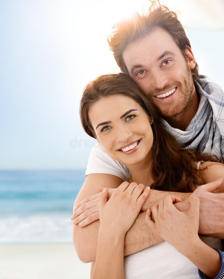 Glückliche junge Paare, die auf Sommerstrand umfassen stockfoto