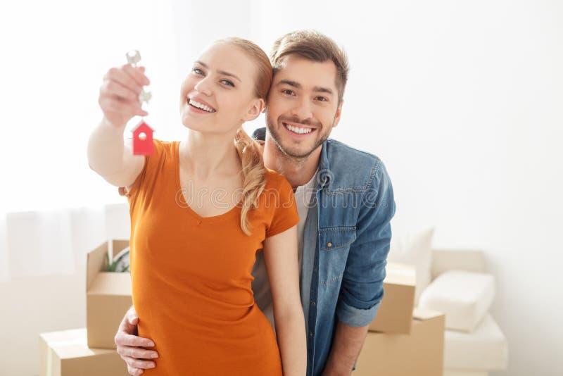Glückliche junge Paare, die beim Schlüssel halten vom Haus lächeln lizenzfreie stockfotografie