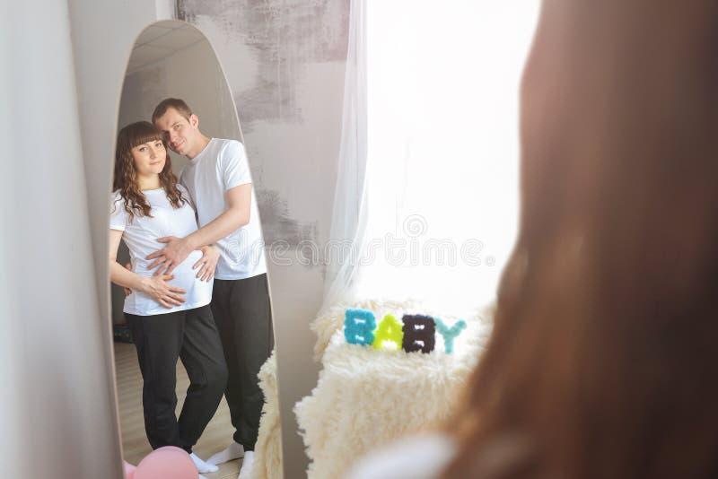Glückliche junge Paare, die das Baby steht zusammen erwarten, umfassend und betrachtend Spiegel Mann, der einen Bauch von seinem  lizenzfreie stockfotos