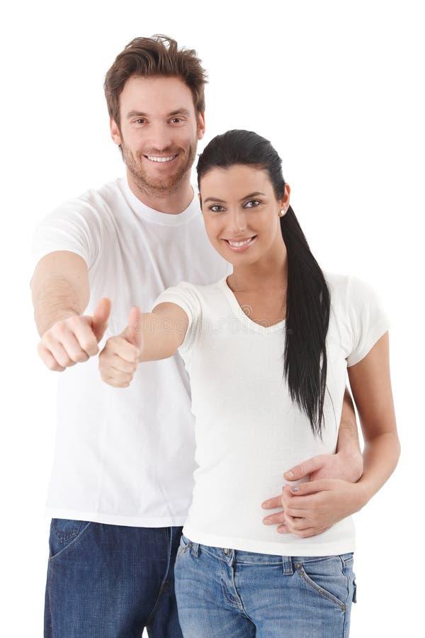 Glückliche junge Paare, die Daumen zeigend lächeln stockbild