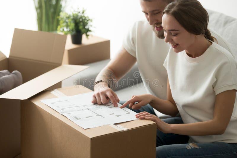 Glückliche junge Paare, die den Plan plant neues Hauptdesign betrachten lizenzfreie stockfotografie
