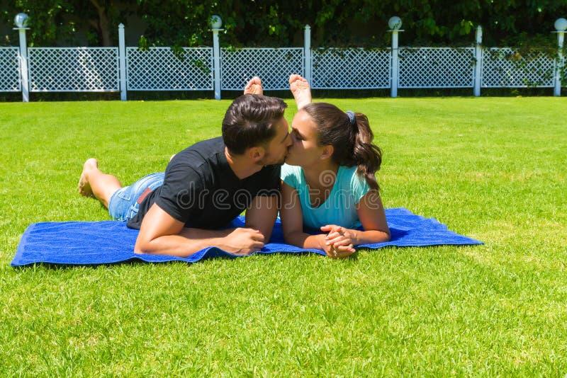 Glückliche junge Paare, die die Sonne genießend sich entspannen stockfotografie