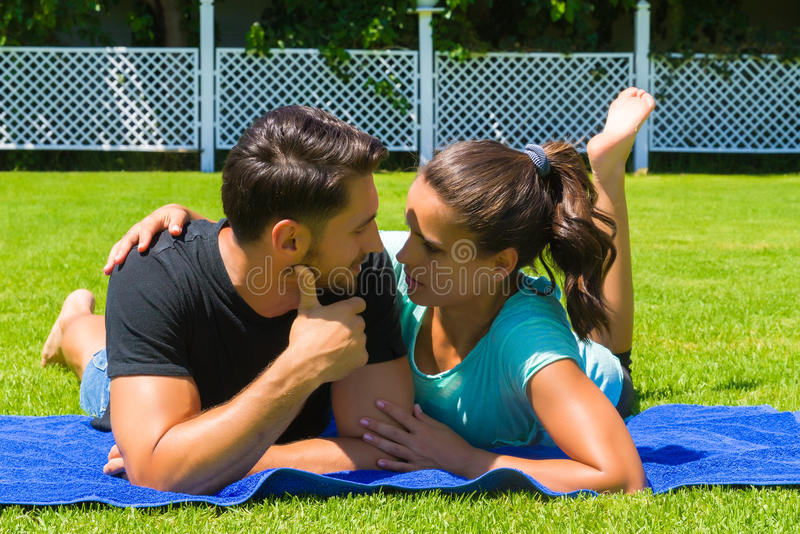 Glückliche junge Paare, die die Sonne genießend sich entspannen stockbild