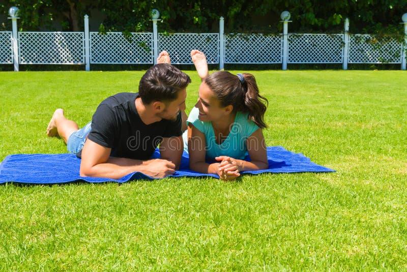 Glückliche junge Paare, die die Sonne genießend sich entspannen lizenzfreies stockbild