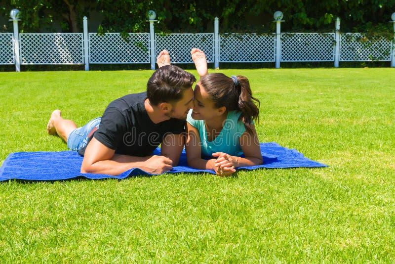 Glückliche junge Paare, die die Sonne genießend sich entspannen stockfotos