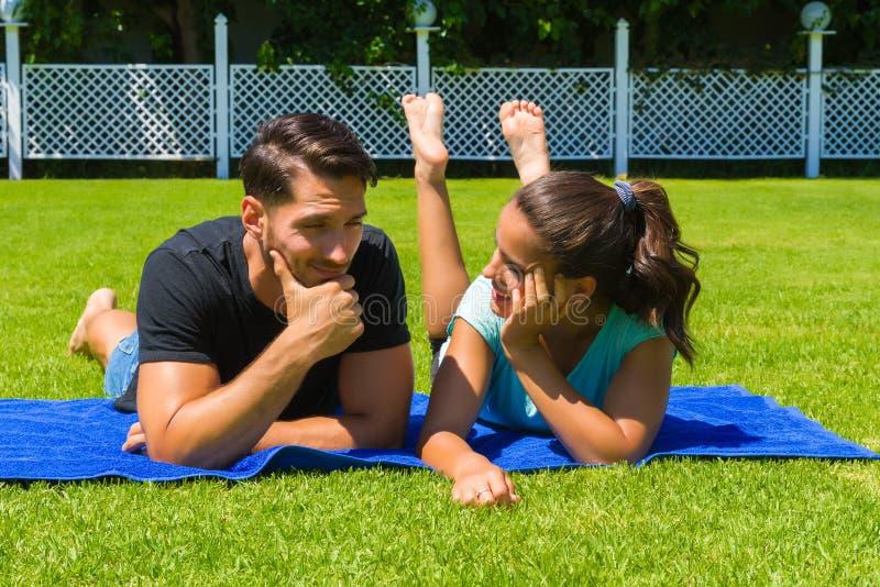 Glückliche junge Paare, die die Sonne genießend sich entspannen lizenzfreies stockfoto