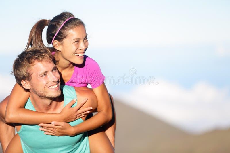 Glückliche junge Paare, die draußen huckepack tragen lizenzfreie stockbilder