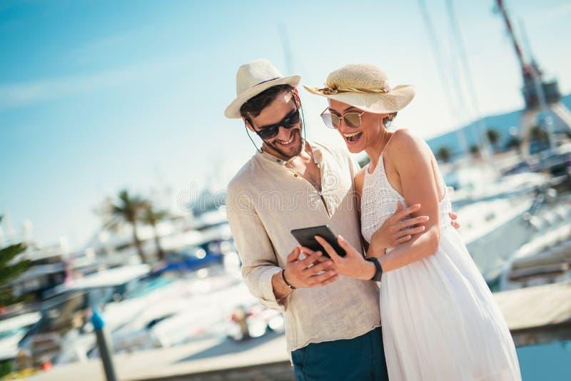 Glückliche junge Paare, die durch den Hafen unter Verwendung der digitalen Tablette gehen lizenzfreies stockfoto